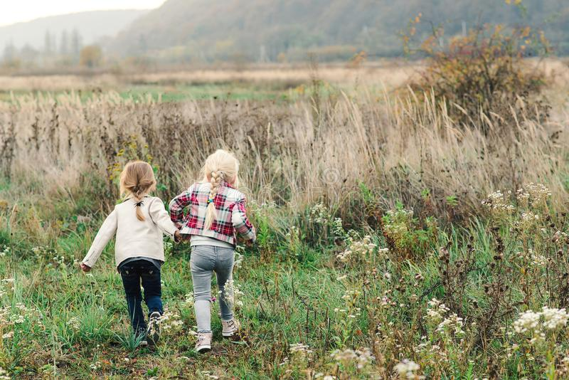 """Χαρούμενες αδελφές που τρέχουν σε ένα χωράφι την ημέρα Ï""""Î¿Ï… φθινοπώρου.  στοκ φωτογραφία"""