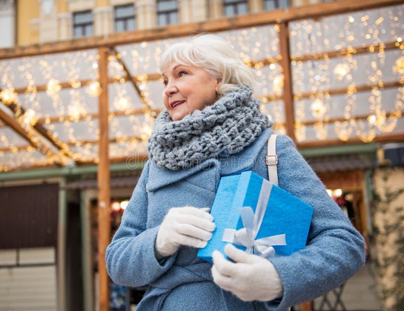 Χαρούμενη ανώτερη γυναίκα που περιμένει με παρόντα υπαίθριο στοκ φωτογραφία