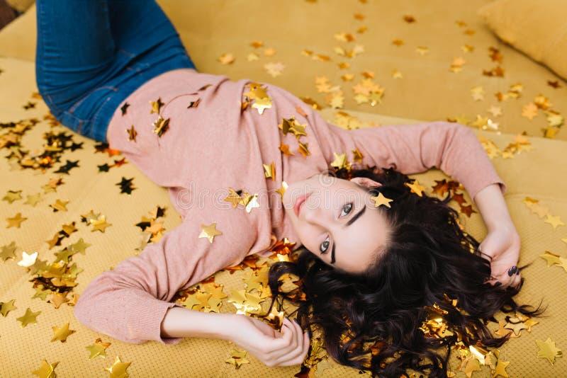 Χαρούμενη αρκετά νέα γυναίκα με τη σγουρή τρίχα brunette που βάζει πίσω στον μπεζ καναπέ χρυσά tinsels Όμορφο πρότυπο στοκ φωτογραφίες με δικαίωμα ελεύθερης χρήσης