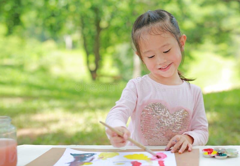 Χαρούμενη ασιάτισσα κοπέλα που κάθεται σε ένα τραπέζι σε έναν καλοκαιρινό κήπο ζωγραφίζοντας πινέλο ζωγραφικής, Εκπαιδευτική τέχν στοκ φωτογραφία