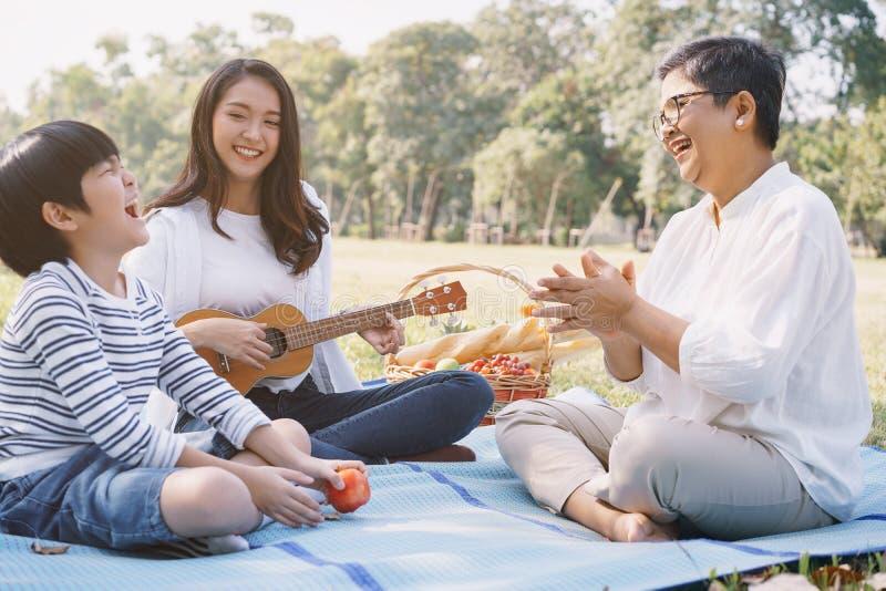 Χαρούμενη ασιατική οικογένεια που διασκεδάζει και διασκεδάζει παίζοντας ukulele στο πάρκο Η έννοια του τρόπου ζωής στις οικογενει στοκ φωτογραφία με δικαίωμα ελεύθερης χρήσης