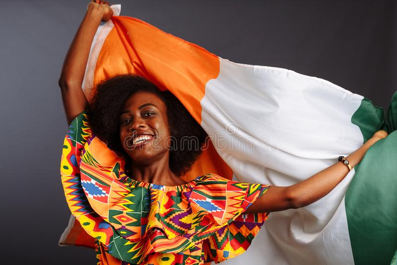 Χαρούμενη αφρικανή με εθνικά ρούχα που χαμογελάει και ποζάρει με μια σημαία Ακτή Ελεφαντοστού, C te d`Ivoire απομονωμένη πάνω από στοκ εικόνα