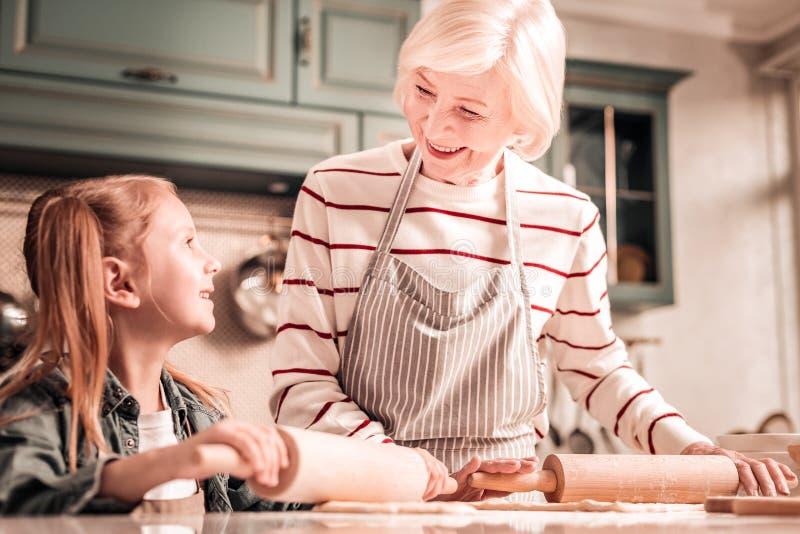 Χαρούμενη γιαγιά που εξετάζει την εγγονή της με την αγάπη στοκ εικόνα