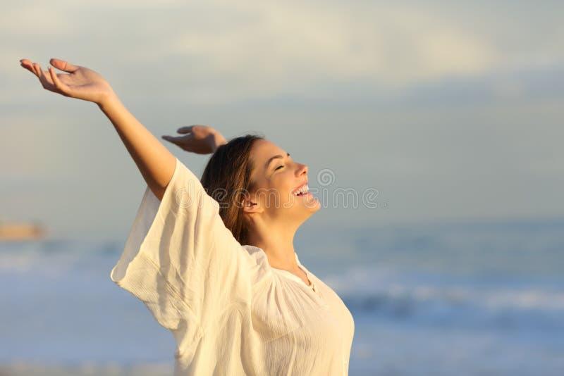 Χαρούμενη γυναίκα που απολαμβάνει μια ημέρα στην παραλία στοκ εικόνες