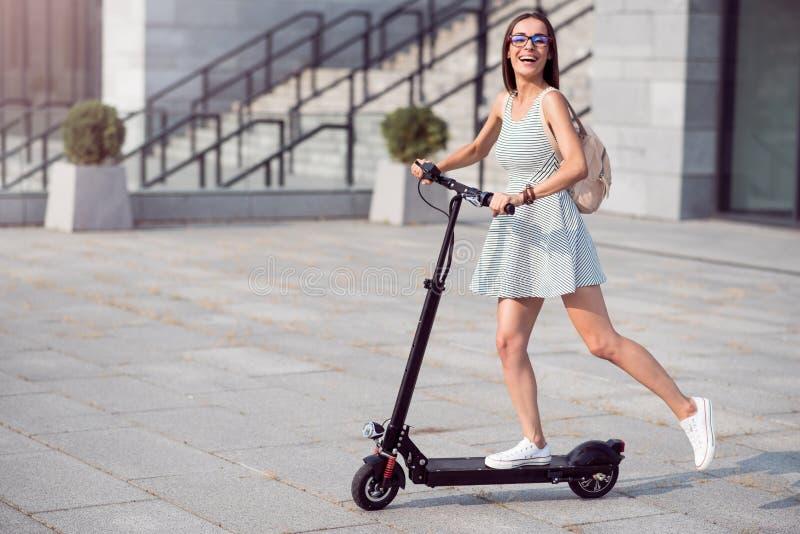 Χαρούμενη γυναίκα που οδηγά ένα μηχανικό δίκυκλο λακτίσματος στοκ φωτογραφίες με δικαίωμα ελεύθερης χρήσης
