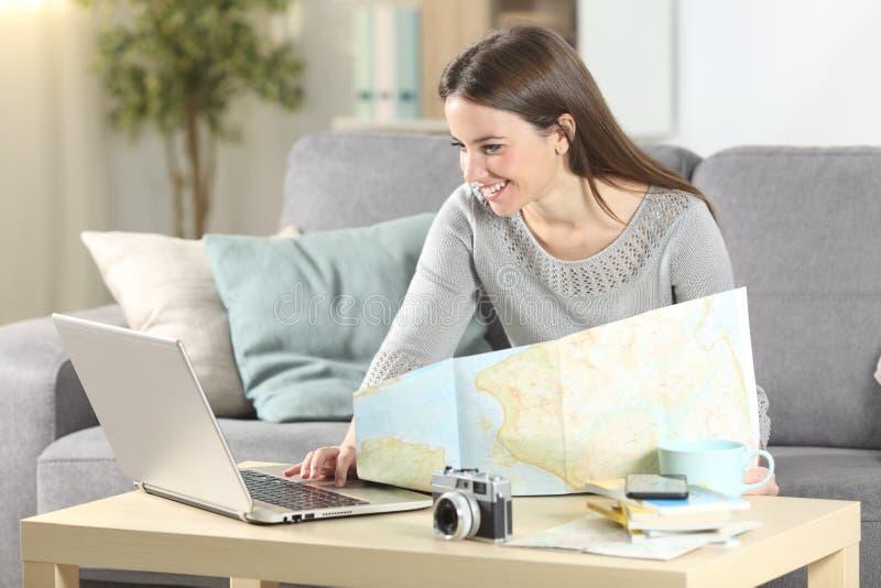 Χαρούμενη γυναίκα που σχεδιάζει διακοπές στο διαδίκτυο στο σπίτι στοκ φωτογραφίες