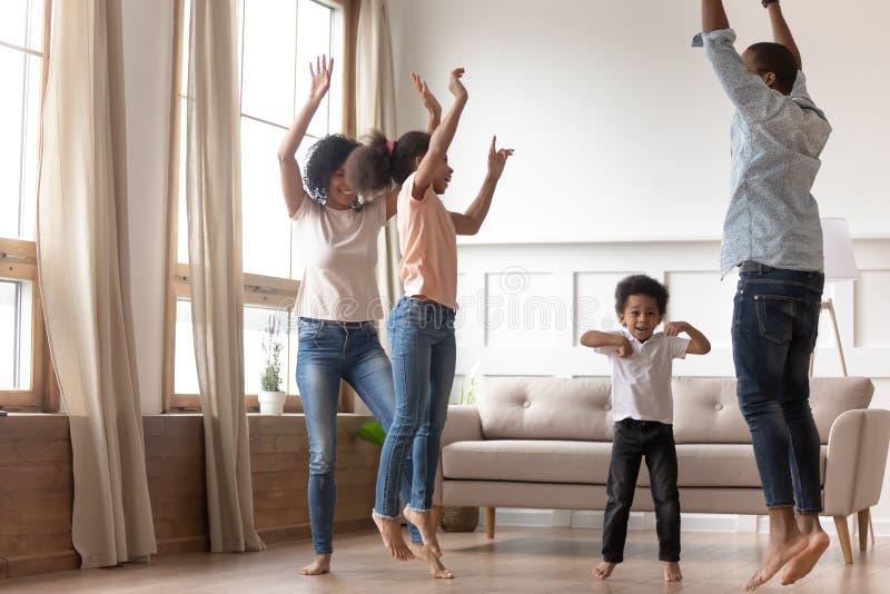 Χαρούμενη ευτυχής αφρικανική οικογένεια που έχει τη διασκέδαση που πηδά στο σπίτι από κοινού στοκ φωτογραφίες