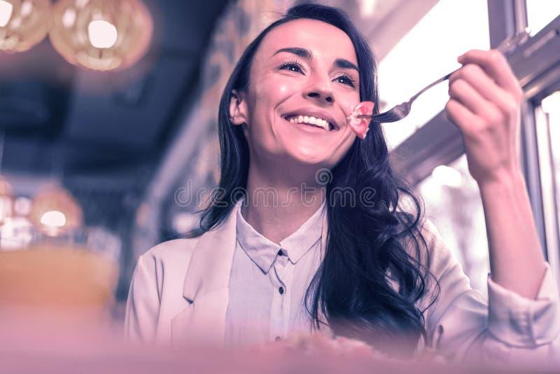 Χαρούμενη θετική συμπαθητική γυναίκα που απολαμβάνει το γεύμα της στοκ εικόνες