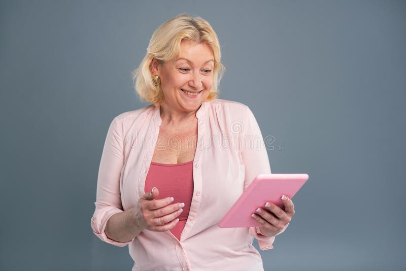 Χαρούμενη μέσης ηλικίας γυναίκα που χαμογελά διαβάζοντας το μήνυμα στοκ εικόνα
