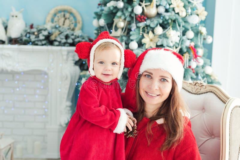 Χαρούμενη μητέρα και κόρη στα χριστουγεννιάτικα καπέλα και με κόκκινο  στοκ εικόνα με δικαίωμα ελεύθερης χρήσης