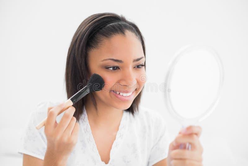 Χαρούμενη νέα σκοτεινή μαλλιαρή πρότυπη να ισχύσει σκόνη στο πρόσωπό της στοκ εικόνες