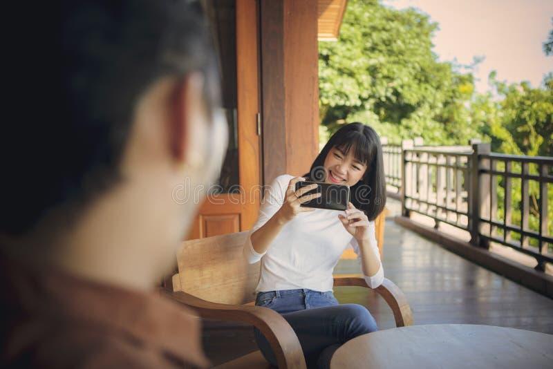 Χαρούμενη νεαρή ασιάτισσα γυναίκα που τραβάει μια φωτογραφία από το έξυπνο τηλέφωνο με συναίσθημα ευτυχίας στοκ εικόνα με δικαίωμα ελεύθερης χρήσης
