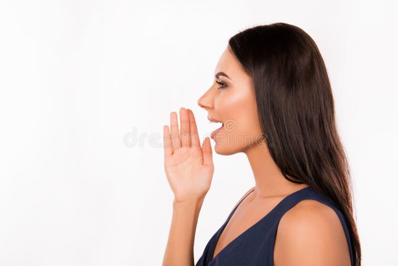 Χαρούμενη νεαρή γυναίκα που ανακοινώνει κάτι κρατώντας το χέρι κοντά στο στόμα στοκ φωτογραφίες