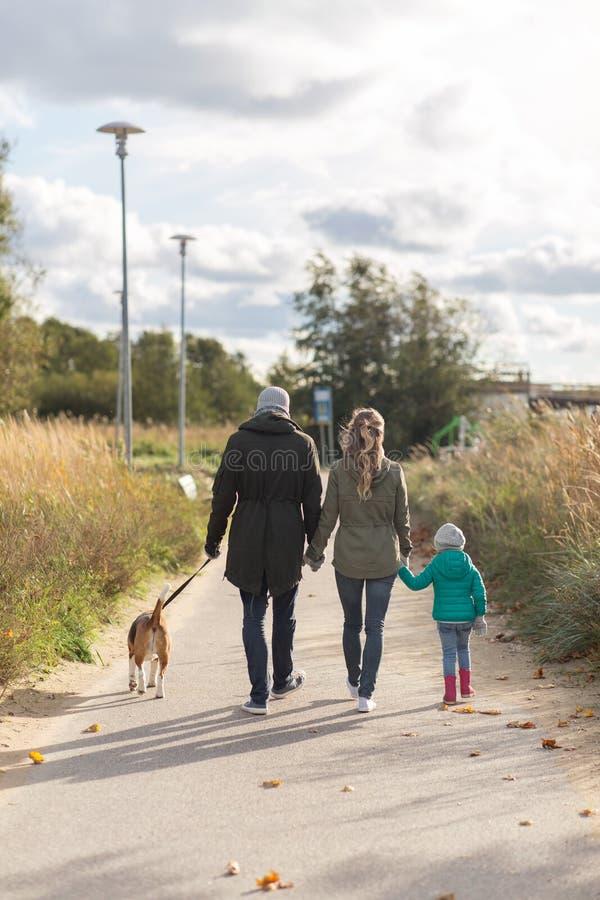 Χαρούμενη οικογένεια που περπατάει με σκύλο το φθινόπωρο στοκ φωτογραφία με δικαίωμα ελεύθερης χρήσης