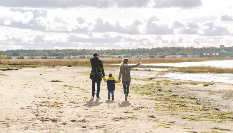 Χαρούμενη οικογένεια που περπατάει στην παραλία του φθινοπώρου στοκ φωτογραφία με δικαίωμα ελεύθερης χρήσης