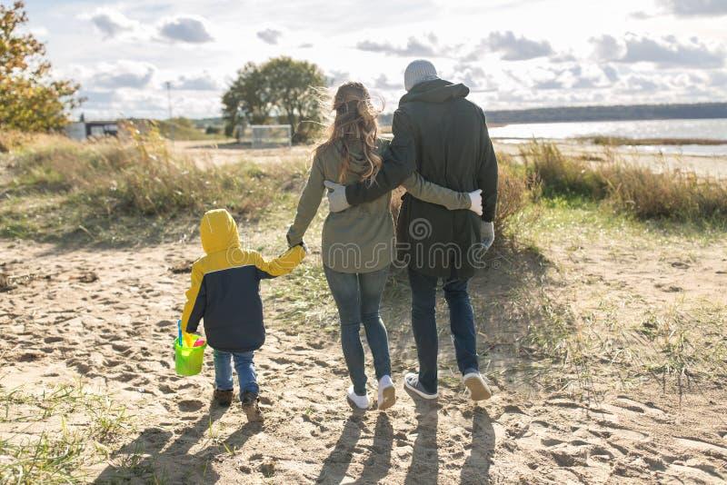 Χαρούμενη οικογένεια που περπατάει στην παραλία του φθινοπώρου στοκ φωτογραφία