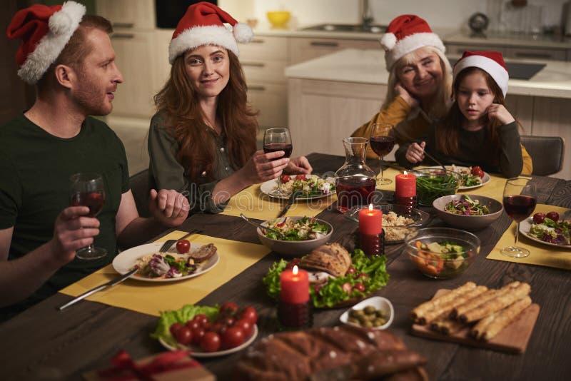 Χαρούμενη οικογένεια που συλλέγει για το εορταστικό γεύμα στοκ εικόνες