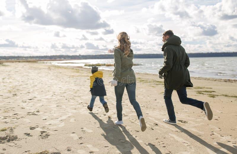 Χαρούμενη οικογένεια που τρέχει στην παραλία του φθινοπώρου στοκ φωτογραφία με δικαίωμα ελεύθερης χρήσης