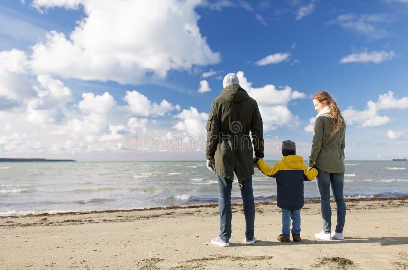 Χαρούμενη οικογένεια στην παραλία το φθινόπωρο κοιτάζοντας τη θάλασσα στοκ εικόνες