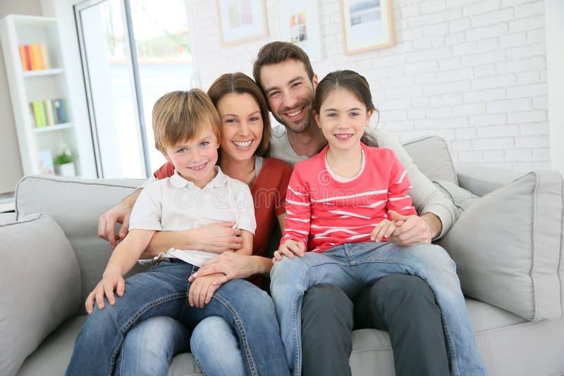 Χαρούμενη οικογενειακή συνεδρίαση στο σπίτι στον καναπέ στοκ φωτογραφία με δικαίωμα ελεύθερης χρήσης