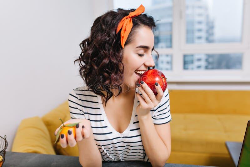 Χαρούμενη συγκινημένη νέα γυναίκα πορτρέτου με τη σγουρή τρίχα περικοπών που απολαμβάνει το κόκκινο μήλο στο σύγχρονο διαμέρισμα  στοκ φωτογραφία