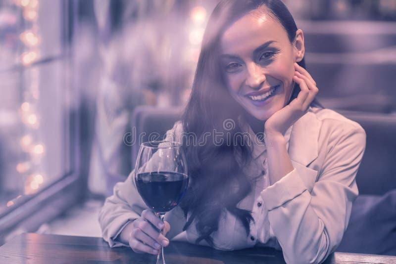 Χαρούμενη συμπαθητική γυναίκα που πίνει το κόκκινο κρασί μόνο στοκ εικόνες