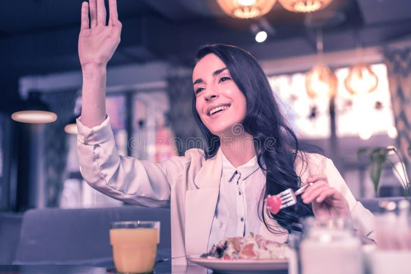 Χαρούμενη συμπαθητική νέα γυναίκα που αυξάνει το χέρι της επάνω στοκ εικόνες με δικαίωμα ελεύθερης χρήσης