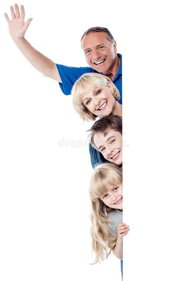 Χαρούμενη τετραμελής οικογένεια πίσω από το κενό whiteboard στοκ εικόνες με δικαίωμα ελεύθερης χρήσης