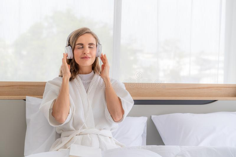 Χαρούμενη όμορφη γυναίκα στα ακουστικά που ακούει μουσική και τραγουδΠστοκ φωτογραφίες