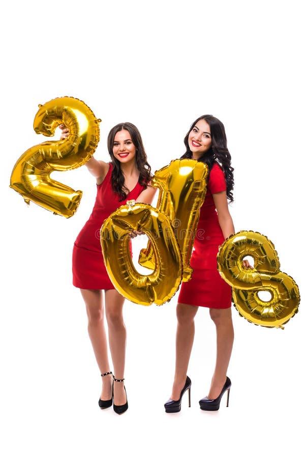 Χαρούμενοι και ευτυχείς νέοι γυναικών πλήρεις ύψους αριθμοί 2018 μπαλονιών εκμετάλλευσης χρυσοί ως σύμβολο του νέου έτους στο άσπ στοκ φωτογραφία