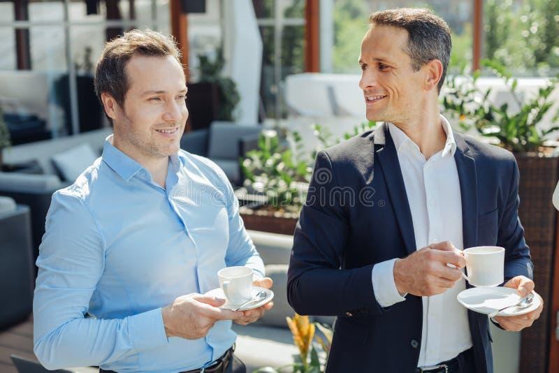 Χαρούμενοι συμπαθητικοί επιχειρηματίες που απολαμβάνουν τον καφέ τους στοκ φωτογραφία με δικαίωμα ελεύθερης χρήσης
