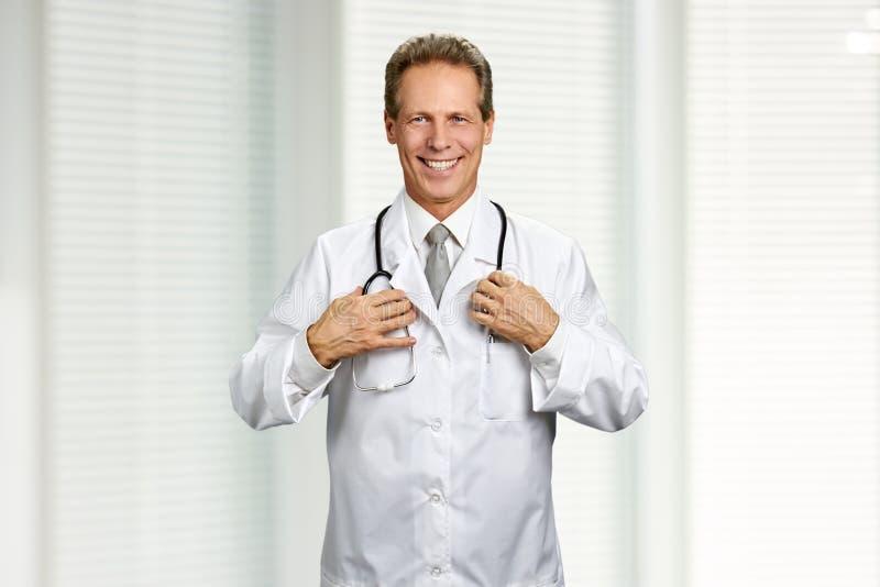 Χαρούμενος αρσενικός γιατρός με το στηθοσκόπιο στοκ εικόνα
