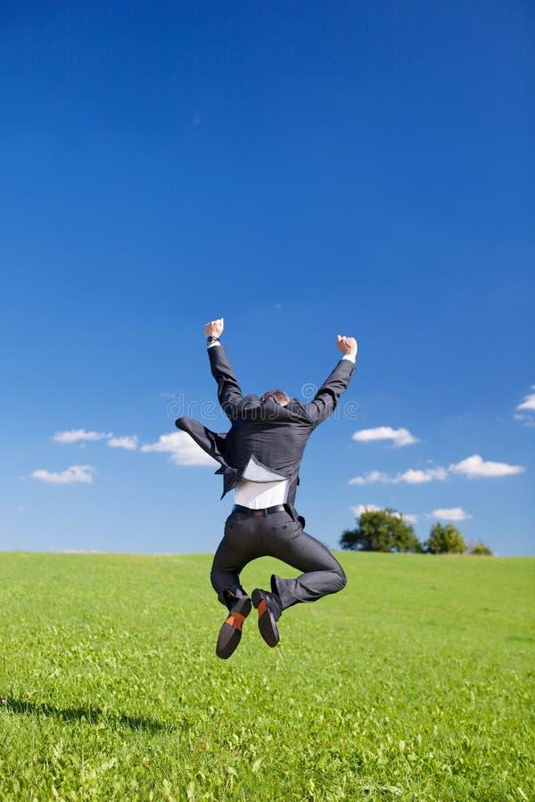 Χαρούμενος επιχειρηματίας που πηδά για τη χαρά στοκ εικόνα