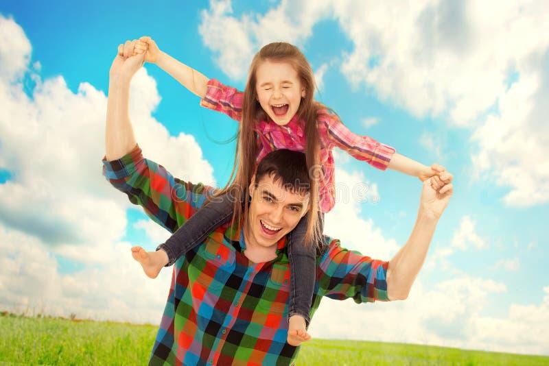 Χαρούμενος πατέρας με την κόρη στους ώμους στοκ εικόνες