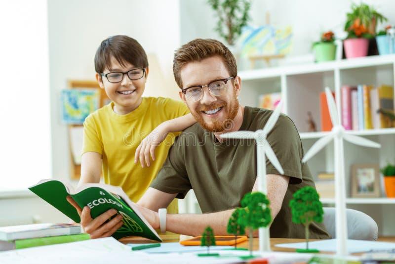 Χαρούμενος περίεργος δάσκαλος που εξηγεί τις ευκαιρίες σπουδαστών ανεμόμυλών του στοκ εικόνα με δικαίωμα ελεύθερης χρήσης