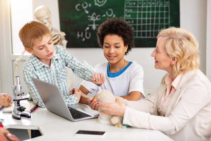 Χαρούμενος προοδευτικός δάσκαλος που μιλά στους σπουδαστές της στοκ εικόνες