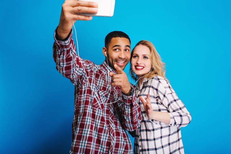 Χαρούμενος όμορφος τύπος που κάνει selfie το πορτρέτο με την αρκετά νέα ξανθή γυναίκα στο μπλε υπόβαθρο Κατοχή της διασκέδασης, μ στοκ φωτογραφία με δικαίωμα ελεύθερης χρήσης