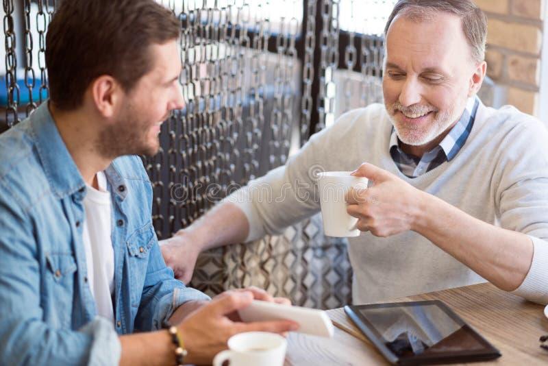 Χαρούμενο άτομο και ο ενήλικος καφές κατανάλωσης εγγονών του στοκ φωτογραφία με δικαίωμα ελεύθερης χρήσης