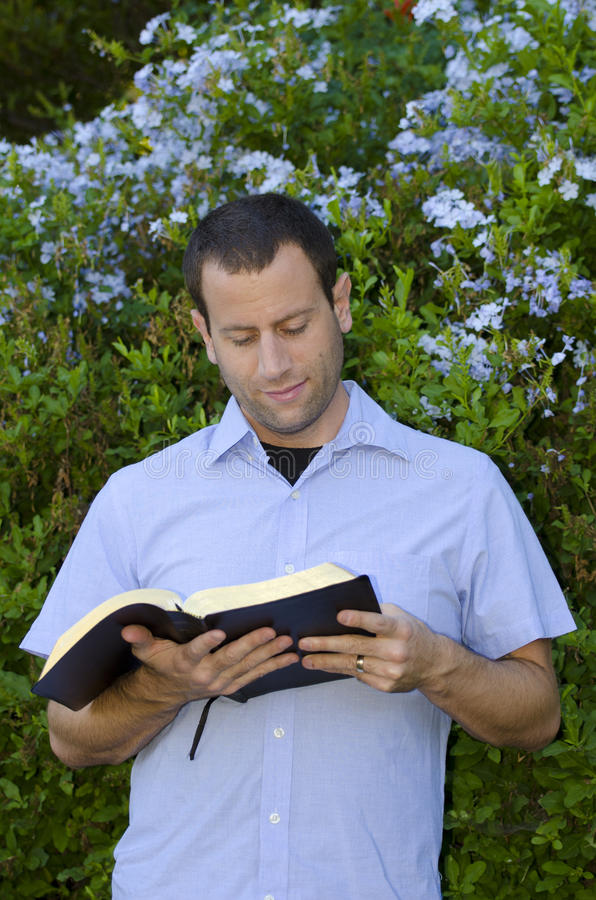 Χαρούμενο άτομο που διαβάζει τη Βίβλο έξω στοκ εικόνα με δικαίωμα ελεύθερης χρήσης