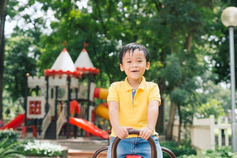 Χαρούμενο αγόρι στο οδηγώντας παιχνίδι ηλικίας δημοτικών σχολείων στην παιδική χαρά παιδιών ` s στοκ εικόνα
