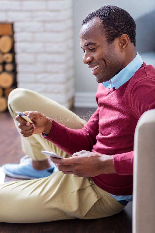 Χαρούμενο ευτυχές άτομο που εξετάζει τους αριθμούς πιστωτικής κάρτας στοκ εικόνες με δικαίωμα ελεύθερης χρήσης