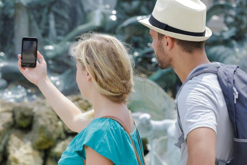 Χαρούμενο ζευγάρι που ταξιδεύει βγάζοντας φωτογραφίες με κινητό τηλέφωνο στοκ εικόνα