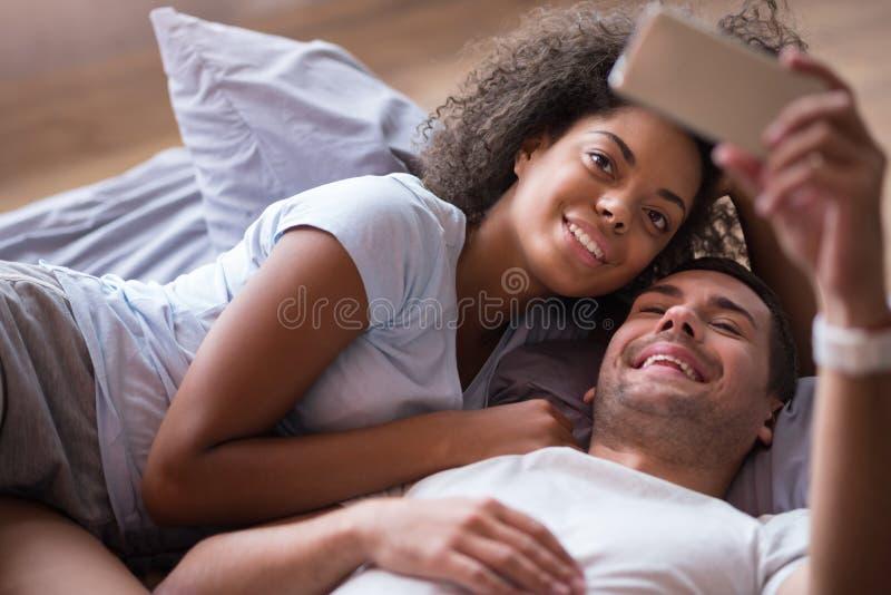 Χαρούμενο ζεύγος που παίρνει τη φωτογραφία μαζί στο κρεβάτι στοκ φωτογραφίες με δικαίωμα ελεύθερης χρήσης