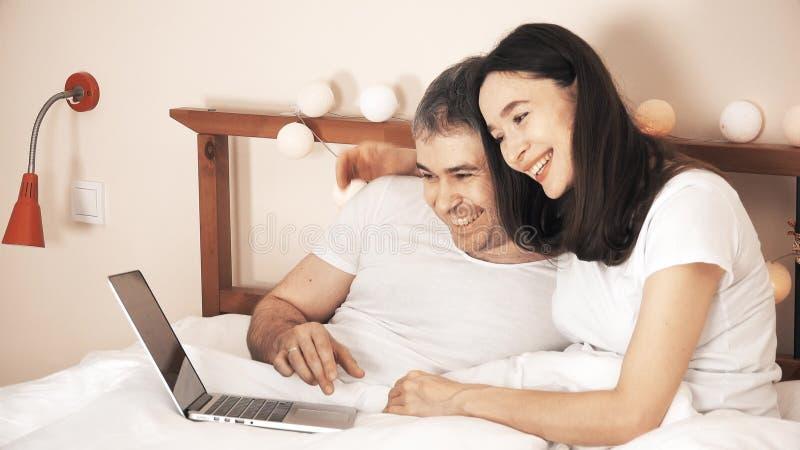 Χαρούμενο ζεύγος που χρησιμοποιεί το lap-top τους στο κρεβάτι στο σπίτι στοκ φωτογραφία