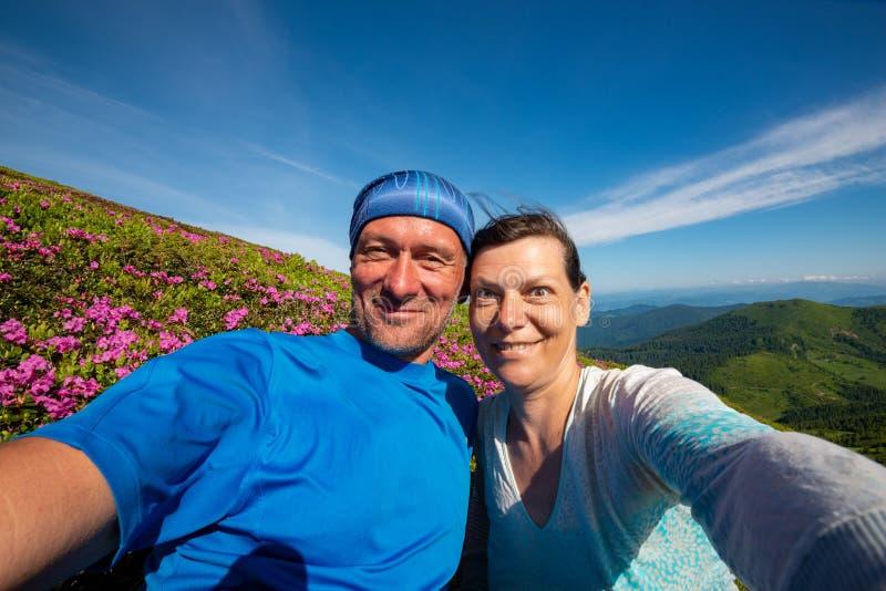 Χαρούμενο ζεύγος των τυχοδιωκτών που παίρνουν selfie και που έχουν τη διασκέδαση στοκ εικόνες