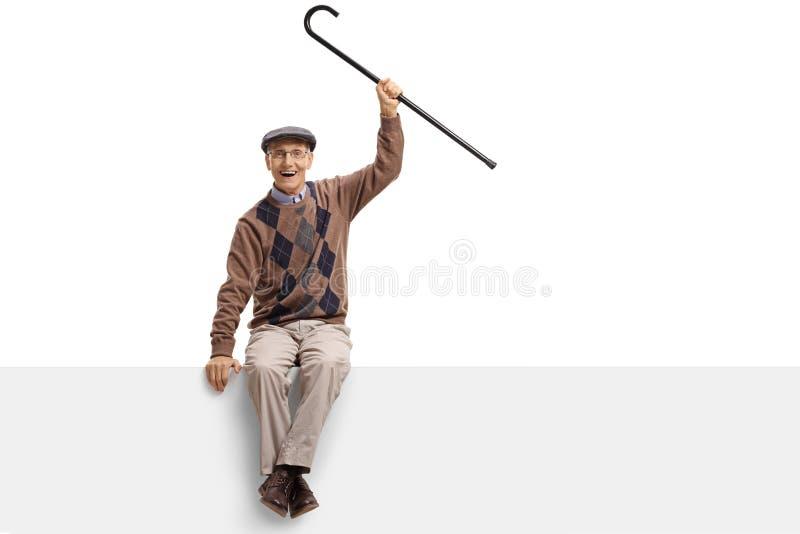 Χαρούμενο ηλικιωμένο άτομο με μια συνεδρίαση καλάμων σε μια επιτροπή στοκ φωτογραφίες