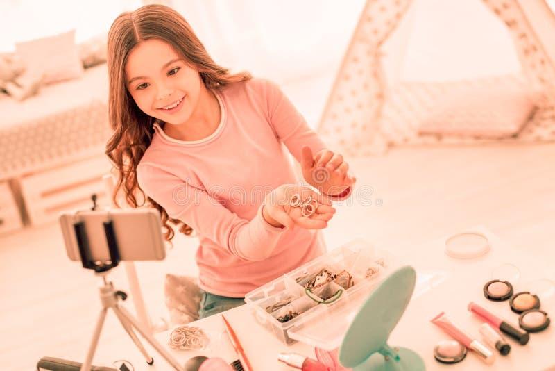 Χαρούμενο θετικό κορίτσι που παρουσιάζει δαχτυλίδια της στους θεατές στοκ εικόνα