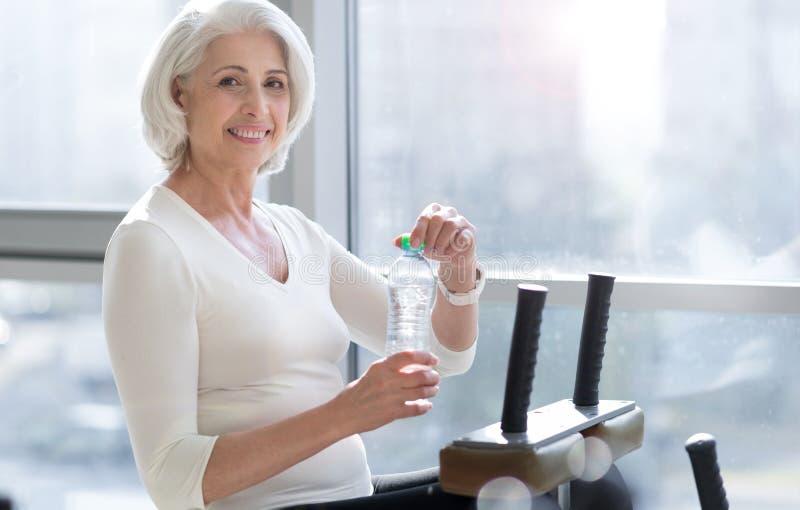 Χαρούμενο κατάλληλο ανώτερο πόσιμο νερό γυναικών κατά τη διάρκεια του workout στοκ φωτογραφίες με δικαίωμα ελεύθερης χρήσης