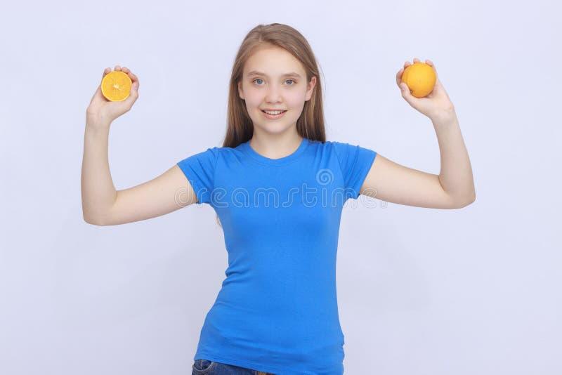 Χαρούμενο κορίτσι εφήβων με το πορτοκάλι στοκ φωτογραφία με δικαίωμα ελεύθερης χρήσης