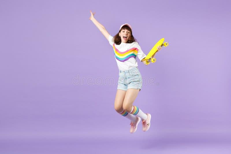 Χαρούμενο κορίτσι εφήβων στα ζωηρά ενδύματα που κρατά κίτρινο skateboard, που έχει τη διασκέδαση, άλμα, χέρια διάδοσης που απομον στοκ φωτογραφία
